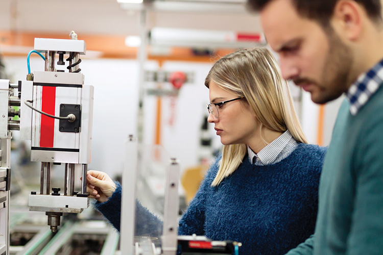 Business casually dressed man and woman look at hi-tech manufacturing components