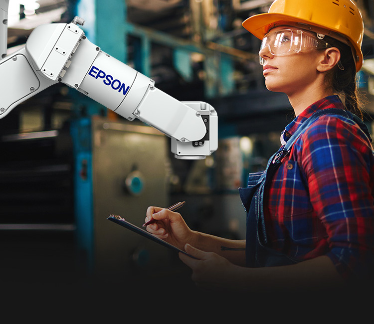 Woman wearing a hardhat and safety glasses in front of a robotic arm